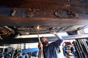 Booneville, Kentucky: Mechanic welds a pipe at his auto repair shop in Owsley County