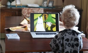 A two year old boy watching children's tv on laptop
