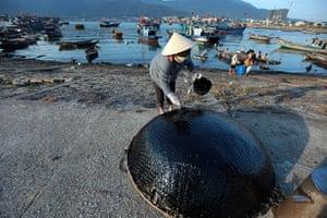 24 hours: Danang, Vietnam: A woman paints asphalt on her 'guffa' fishing boat