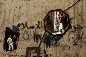 24 hours: Gaza City: Palestinians are reflected in mirrors outside their store
