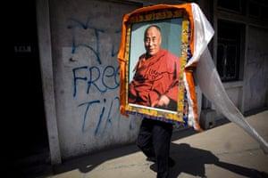 24 hours: Kathmandu, Nepal: An exiled Tibetan holds a portrait of the Dalai Lama