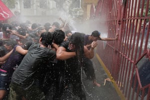 24 hours: Manila, Philippines: Protesters hold on as they are hit by water cannon