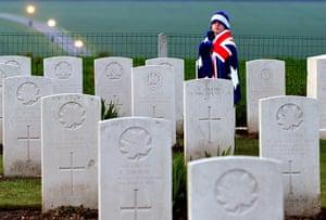 Anzac Day: A child wearing an Australian flag walks past graves in Villers-Bretonneux