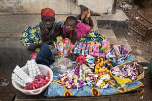Sierra Leone after Taylor: Two girls sell sweets watch from their makeshift kiosk in Makeni