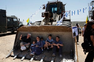 Picture Desk Live: An Israeli family poses for a picture as they sit on a military bulldozer