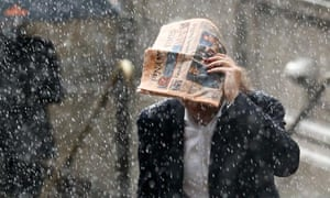 A man tries to shelter under a copy of the Financial Times
