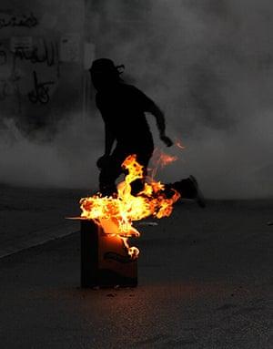 Picture desk live: A Bahraini anti-government protester runs from tear gas