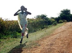 South Sudan: A woman runs along a road during an air strike by the Sudanese air force