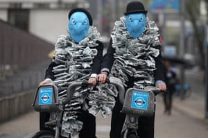 Picture desk live: Protesters dressed as suited eagles on Barclays cycle hire bikes