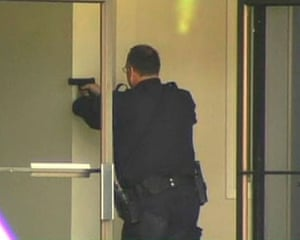 Oakland shootings: A police officer aims his pistol inside a building at Oikos University
