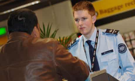 A UK Border Force officer works at a passport control desk in Terminal 3 at Heathrow airport