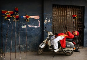24 hours: New Delhi, India: A marching band member sleeps on a scooter