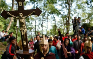 Good Friday traditions: Wonogiri, Central Java: A worshipper carries a crucifix