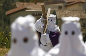 Good Friday traditions: Villarosa, Sicily: Penitents carry a cross during a Good Friday procession