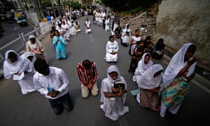 Good Friday traditions: Jammu, India: Christians kneel and offer prayers during a procession