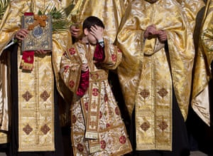 Easter Sunday: A boy covers his face during an orthodox Palm Sunday pilgrimage, Bucharest