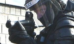 Policeman prepares to fire a baton round