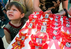 May Day 2012: Kiev: A Ukrainian boy helps his mother to sell traditional red bows