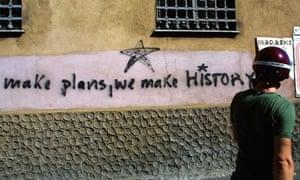 "demonstrator passes by slogan reading ""make plans, we make history"""