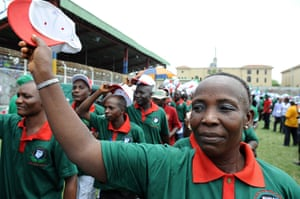 May Day rallies 2012: Lagos, Nigeria:A woman raises her cap as workers march to salute