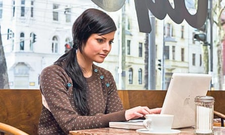 Young Woman in Cafe Using a Laptop
