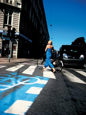 Big Picture, bikes: Big picture: Woman walking a bike across a blue crossing also wearing blue