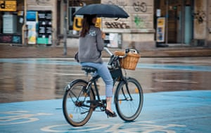 Big Picture, bikes: Big Picture: woman cycling whilst holding an umbrella