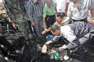 Damascus Bombs: Men clear debris at a security compound where the bombs exploded