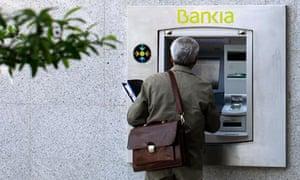 A man uses a Bankia cash dispenser