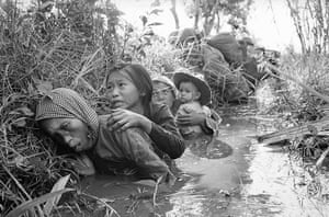 Horst Faas gallery: Women and children crouch in a muddy canal