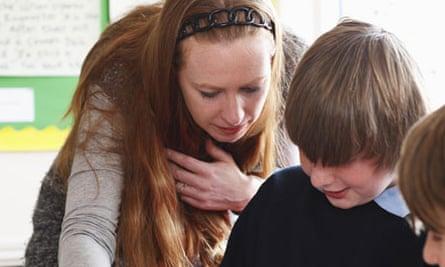Female teacher explaining problem to two boys in school uniform