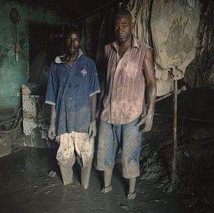 Drowning World: Workers Ledix Finep and Jeanvier Cassimer pause to as they clear the mud