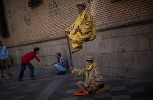 24 hours: Madrid, Spain: Men perform as they beg for charity in a street