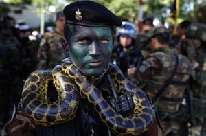 24 hours: Asuncion, Paraguay: A Marine officer poses for a photo with a snake