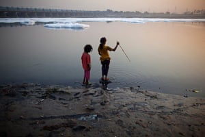 24 hours: New Delhi, India: Girls stand next to the waters of the river Yamuna