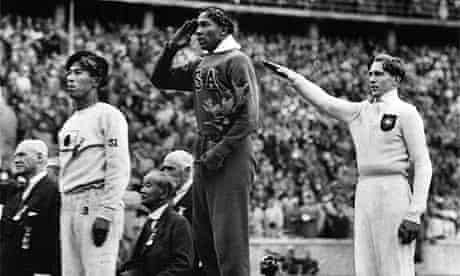American Jesse Owens salutes during the long jump medal ceremony at the Berlin Olympics