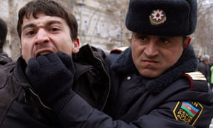 A policeman detains an opposition activist in Baku