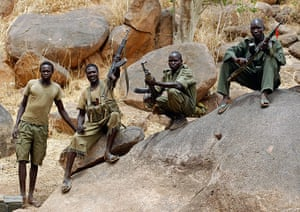 Nuba Mountains Conflict: A SPLA-N fighter holds up his rifle near Jebel Kwo village, Nuba Moutnains
