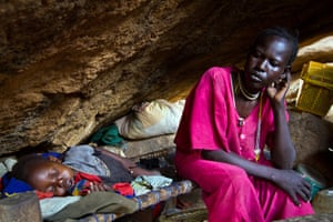 Nuba Mountains Conflict: A mother rests with her child in a cave outside of Tess