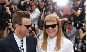 Ewan McGregor and Andrea Arnold in sunglasses smiling with bank of photographers behind them