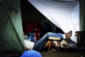 24 hours: An asylum seeker rests inside a tent outside the application center