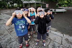 Solar eclipse: Children watch an annular solar eclipse in Fujisawa, near Tokyo