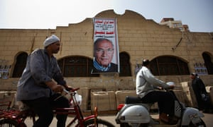 Egyptian's ride past a poster of presidential candidate Ahmed Shafiq