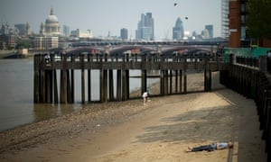 A man soaks up the sun on the south bank of the River Thames