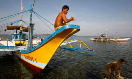 A Filipino fisherman sits on the hull of his boat after arriving from Scarborough Shoal in Masinloc
