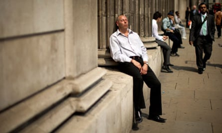 A man soaks up the sun outside the Bank of England