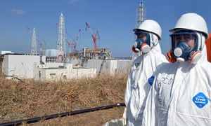 Fukushima Daiichi workers stand near the nuclear power plant during a press tour in February 2012