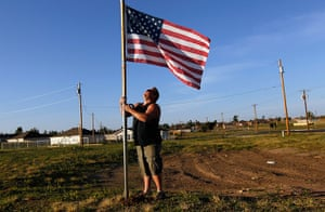FTA: Joe Raedle: A man places an American flag next to where his house was