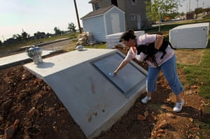 FTA: Joe Raedle: A woman shows off her newly built tornado shelter behind her home