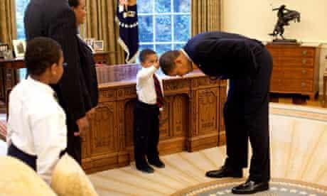 Barack Obama bends over as Jacob Philadelphia pats his head, 2009